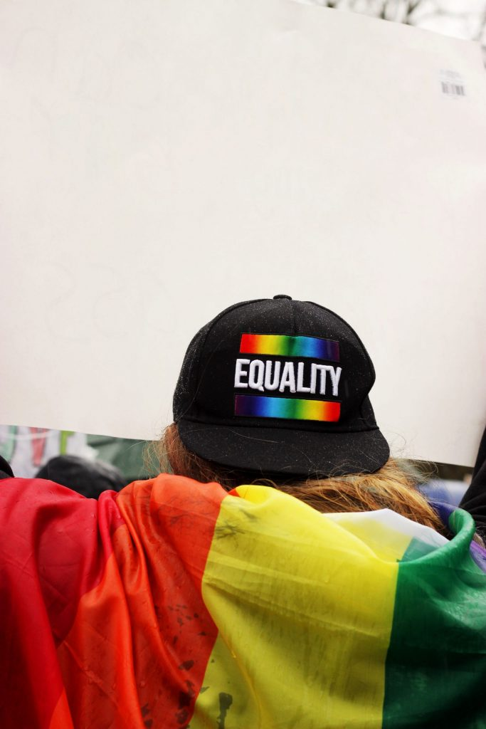 A person at a pride event with a rainbow hat that says equality. Representing lgbtq counseling.