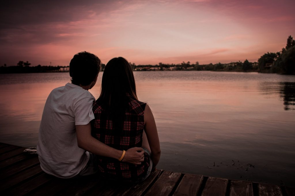 A couple sitting on a dock together looking out on the water and sunset