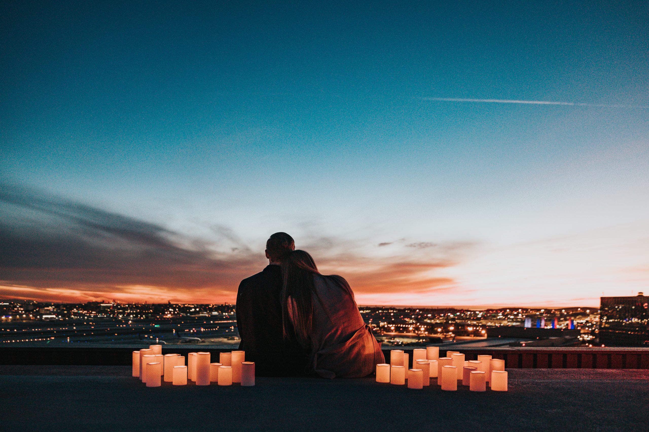 Couple sitting and overlooking the city during sunset