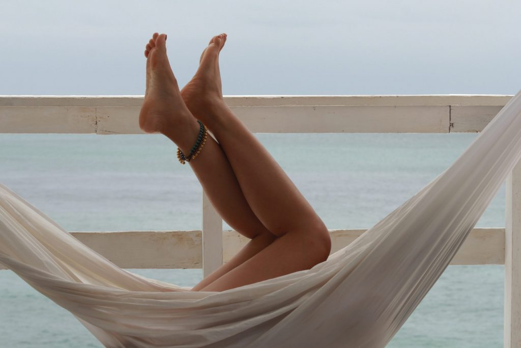 Woman laying in a hammock overlooking the ocean