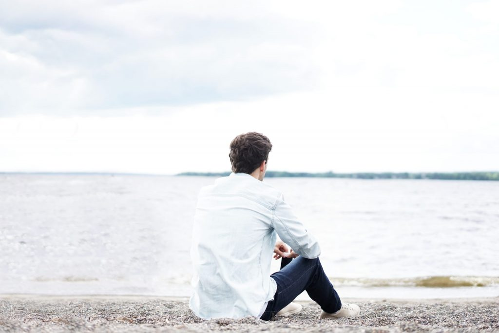 Man sitting on the shore and looking out at the water.