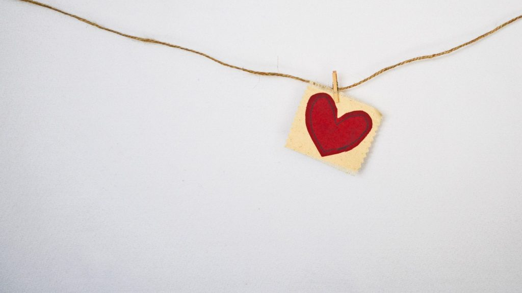 Piece of paper with a heart drawn on it, hanging on a string