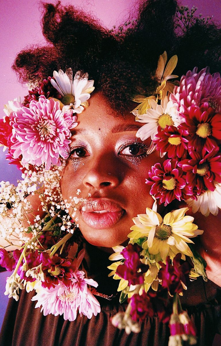 Woman's face surrounded by flowers to represent support groups for women