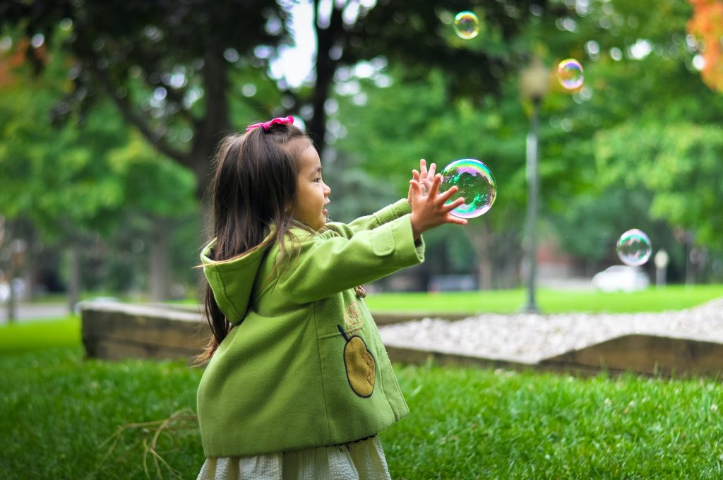 Young girl outside with her hands about to catch a bubble.